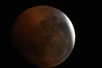 De maansverduistering op 27 juli 2018. Veroorzaakt doordat de maan in de schaduw van de aarde zit. De maan krijgt hierdoor een rode gloed. Het meest rechter stuk van de maan zit al weer in de volle zon.